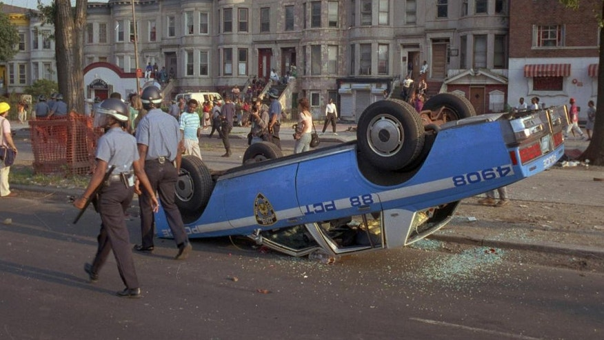 FILE - In this Aug. 21, 1991, file photo, New York Police Department officers, in riot gear, walk past a police car that was overturned by rioters in the Crown Heights section of the Brooklyn borough of New York. A plan to mark the 25th anniversary of the Crown Heights riot with a family-friendly street festival has drawn criticism from the brother of a rabbinical student who suffered a fatal knife wound during the unrest. Organizers say the idea of the festival is to foster a sense of unity in the neighborhood. (AP Photo/David Burns, File)