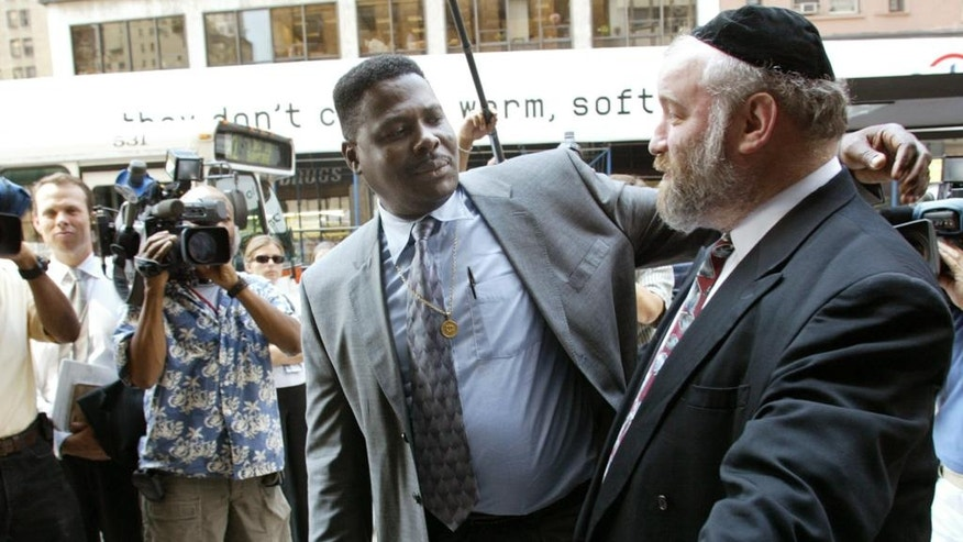 FILE - In this Aug. 19, 2002, file photo, Carmel Cato, center, reaches out to embrace Norman Rosenbaum, right, as they walk together in a show of unity into a New York restaurant on the 11th anniversary of the 1991 Crown Heights riots sparked by the deaths of Cato's 7-year-old son Gavin Cato and the murder of Rosenbaum's brother Yankel, an Australian student. On Sunday, Aug. 21, 2016, residents of the Crown Heights neighborhood in Brooklyn mark the 25th anniversary of the riot. (AP Photo/Beth A. Keiser, File)