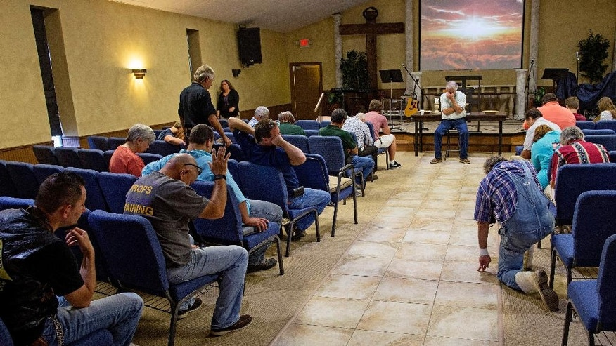 Members of the South Walker Baptist Church led by pastor Mark Carroll, center, pray at the conclusion of what is normally a time for bible study, but which became an informal talk about experiences during the flood in Walker, La., Sunday, Aug. 21, 2016. The church was an island of high ground in a community flooded with 4-5 feet of water a week earlier. During and since the flood the church is serving as a shelter and food distribution point for the community. (AP Photo/Max Becherer)