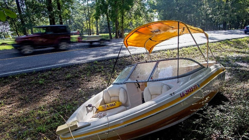An abandoned boat sits by the side of Walker South Road in Walker, La., Sunday, Aug. 21, 2016. Hundreds of residents were rescued from flooded homes in the area last Saturday. (AP Photo/Max Becherer)