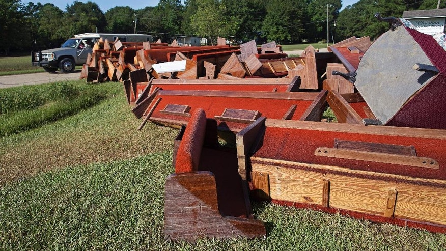 Flood-damaged pews from the Christian Fellowship Church sit on the roadside for trash pick up in Walker, La., Sunday, Aug. 21, 2016. Hundreds of residents were rescued from flooded homes in the area last Saturday. (AP Photo/Max Becherer)