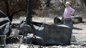 Ki Jo So returns to her home and property burned by the Blue Cut Fire off Highway 138, near Wrightwood, Calif., on Monday, Aug. 22, 2016. So, who has lived on the property for 13 years with her family, had no insurance. (Will Lester/The Sun via AP)
