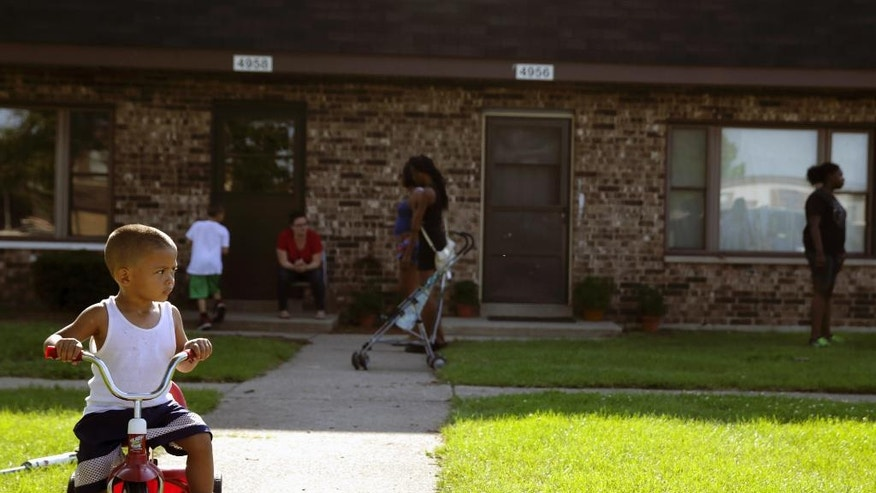 In this Aug. 3, 2016 photo, Joseph Russell, 2, rides his tricycle outside his home at the West Calumet Housing Complex in East Chicago, Ind. More than 1,000 residents of a public housing complex in northwest Indiana have been left in a state of panic and uncertainty since authorities informed them last month that their homes need to be destroyed because of a serious lead contamination threat. (Jonathan Miano/The Times via AP)