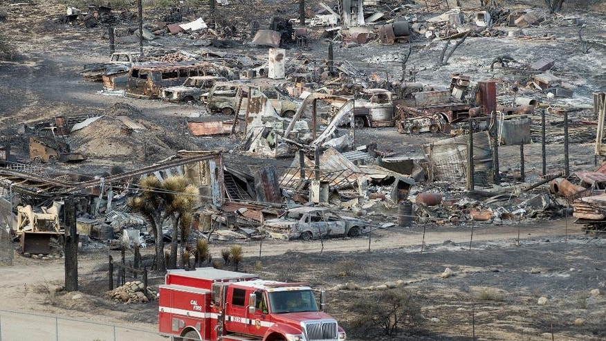 A firetruck passes scorched cars and trailers burned by the Blue Cut fire in Phelan, Calif., on Friday, Aug. 19, 2016. More people returned to their homes Friday as firefighters made significant progress against a huge wildfire burning in Southern California's San Bernardino National Forest, but that was tempered by the announcement that at least 96 homes and 213 outbuildings were destroyed. (AP Photo/Noah Berger)