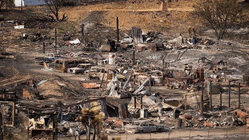 Scorched cars and trailers burned by the Blue Cut fire line a residential street in Phelan, Calif., on Friday, Aug. 19, 2016. Thousands of residents chased from their mountain and desert homes were slowly beginning to take stock of their losses as the preliminary damage assessment was released for the blaze that erupted Tuesday in drought-parched canyons 60 miles east of Los Angeles. (AP Photo/Noah Berger)