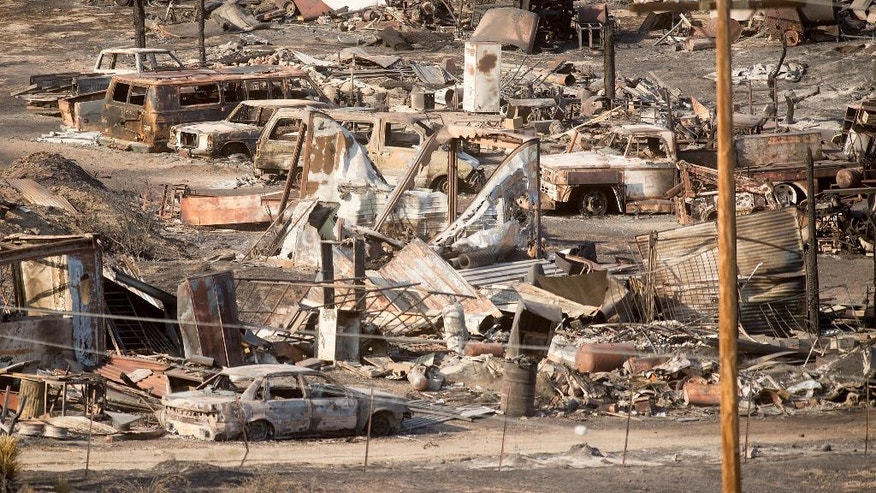 Scorched cars and trailers burned by the Blue Cut fire line a residential street in Phelan, Calif., on Friday, Aug. 19, 2016. More people returned to their homes Friday as firefighters made significant progress against a huge wildfire burning in Southern California's San Bernardino National Forest, but that was tempered by the announcement that at least 96 homes and 213 outbuildings were destroyed. (AP Photo/Noah Berger)