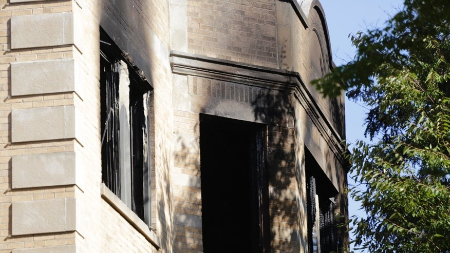 Charred and broken widows can be seen on the third floor of the apartment building after the fire.