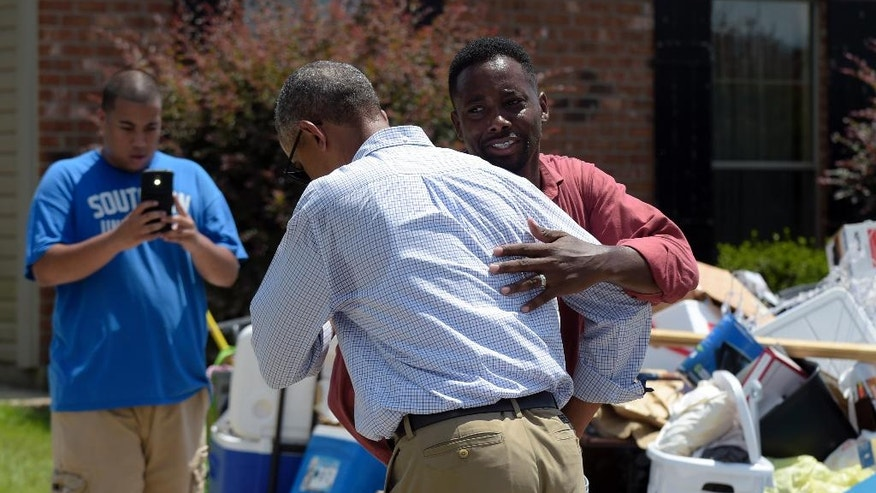 President Barack Obama is greeted as he tours Castle Place, a flood-damaged area of Baton Rouge, La., Tuesday, Aug. 23, 2016. Obama is making his first visit to flood-ravaged southern Louisiana as he attempts to assure the many thousands who have suffered damage to their homes, schools and businesses that his administration has made their recovery a priority. (AP Photo/Susan Walsh)