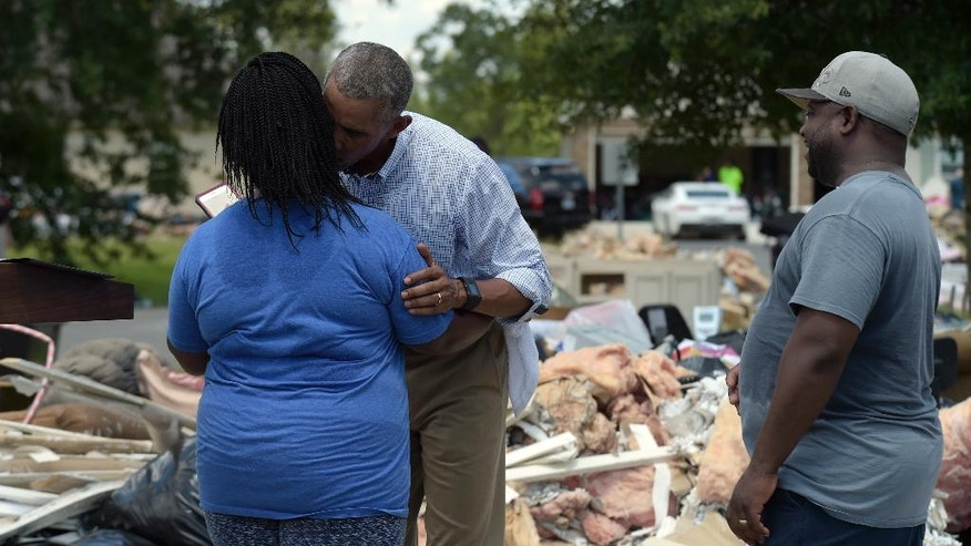 President Barack Obama gives Melissa Williams a kiss as her husband LeRoy Williams watches, during Obama's tours of Castle Place, a flood-damaged area of Baton Rouge, La., Tuesday, Aug. 23, 2016. Obama is making his first visit to flood-ravaged southern Louisiana as he attempts to assure the many thousands who have suffered damage to their homes, schools and businesses that his administration has made their recovery a priority. Obama used the Williams home for his statement about the flooding. (AP Photo/Susan Walsh)