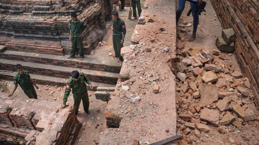 Military personnel stand as they clear debris at a temple that was damaged by a strong earthquake in Bagan, Myanmar, Thursday, Aug. 25, 2016. Using brooms and their hands soldiers and residents of the ancient Myanmar city famous for it's historic Buddhist pagodas, began cleaning up the debris from a powerful earthquake that shook the region and damaged nearly 200 temples Wednesday. (AP Photo/Hkun Lat)