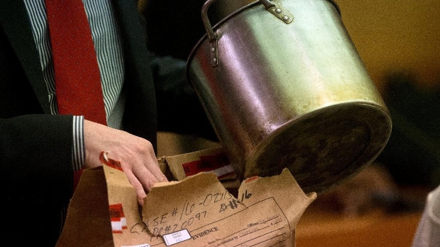 During the trial for Martin Blackwell a lawyer holds a pot they say Blackwell used to pour boiling water on his girlfriend's gay son and his friend as they slept, in Atlanta, Tuesday, Aug. 23, 2016. (AP Photo/John Bazemore)