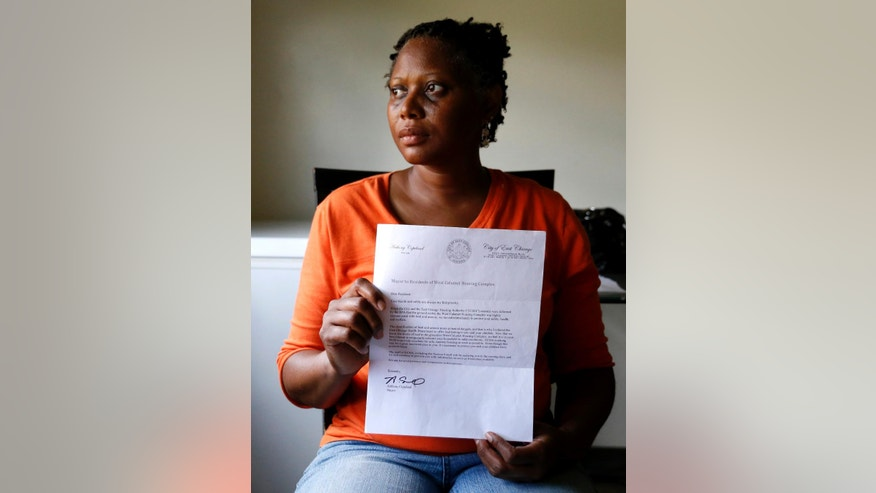 In this Aug. 23, 2016 photo, Sherry Jackson poses for a portrait holding a letter telling her she must relocate from her West Calumet Housing Complex home in East Chicago, Ind. Jackson has lived at West Calumet Housing Complex for 4 years, but will have to move since the the city has decided to demolish the public housing, because of lead contamination. (AP Photo/Tae-Gyun Kim)