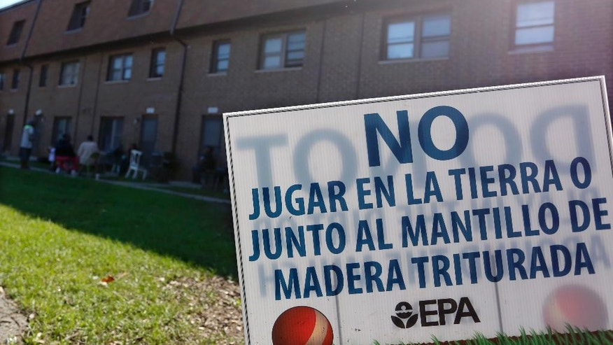 In this Aug. 23, 2016 photo, a sign from the Environmental Protection Agency is posted in front of West Calumet Housing Complex houses at East Chicago, Ind. The EPA has detected high levels of lead in samples of dust and dirt tracked inside homes where soil is tainted with industrial contaminants. The contamination has resulted in the city calling for the demolition of the low-income complex and relocating its 1,000 residents. (AP Photo/Tae-Gyun Kim)