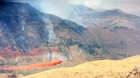 In this photo provided by inciweb.nwcg.gov, a plane drops fire retardant near the northwest side of Owyhee Canyon south of Vale, Ore., Wednesday, Aug. 24, 2016. The nearly 50-square-mile fire in eastern Oregon near the Idaho state line is now threatening Succor Creek State Park. (inciweb.nwcg.gov via AP)