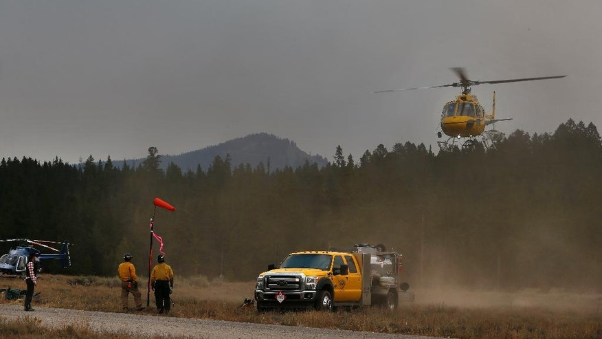 Members of a firefighting crew work at a fire support helicopter staging area south of a wildfire, in north Grand Teton National Park, Wyo., Wednesday, Aug 24, 2016. Some tourists heading to Yellowstone National Park during the busy summer season were facing an hourlong detour Wednesday as a wildfire in neighboring Grand Teton National Park kept a highway closed. (AP Photo/Brennan Linsley)