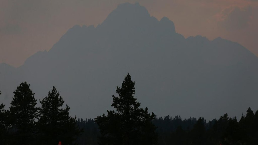 Smoke from a wildfire shrouds a mountain peak in north Grand Teton National Park, Wyo., Wednesday, Aug 24, 2016. Some tourists heading to Yellowstone National Park during the busy summer season were facing an hourlong detour Wednesday as a wildfire in neighboring Grand Teton National Park kept a highway closed. Firefighters hope cooler weather slows the flames over the next couple of days. (AP Photo/Brennan Linsley)