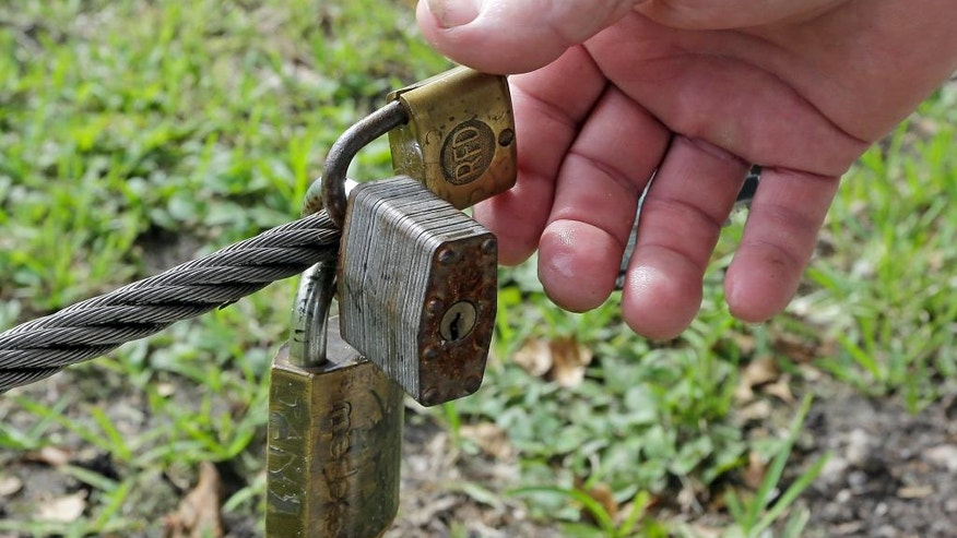 """In this photo taken, Aug., 11, 2016, Mickey Munday shows locks left by people on a fence at Love Park in North Miami, Fla. When he was one of Miami's notorious """"cocaine cowboys"""" in the 1980s, Mickey Munday made millions of dollars flying loads of drugs for Colombia's Medellin and Cali cartels. He knew infamous Medellin kingpin Pablo Escobar. He liked to fly his illicit cargo to out-of-the-way landing strips in the Everglades using high-tech gadgetry such as night-vision goggles. (AP Photo/Alan Diaz)"""