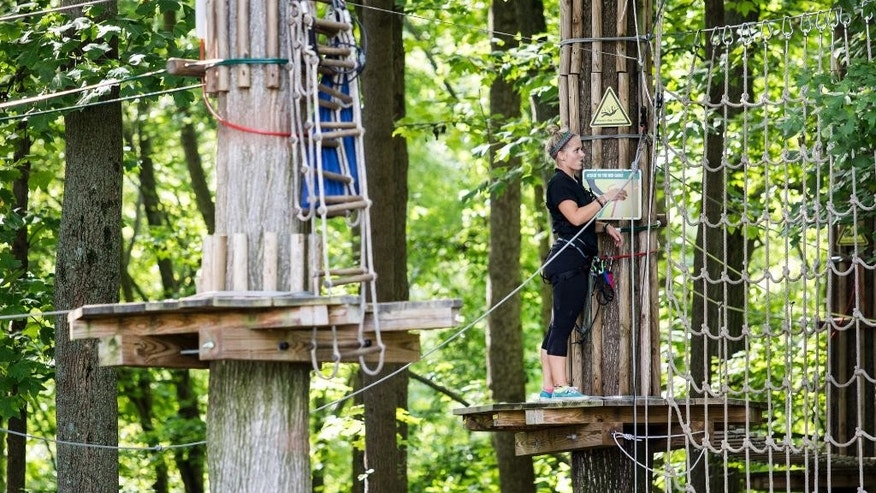 "An employee closes up the Go Ape course for the day after a 59 year-old woman fell to her death at the zip line course in Lums Pond State Park in Bear, Del., Wednesday, Aug. 24, 2016.  Jeff Davis, a spokesman for Go Ape, said Thursday, Aug. 25, 2016, that the rides are inspected on a regular basis. Davis said the Lums Pond attraction is closed for undetermined amount of time to help with the investigation, ""and also in respect to the family of the person who died."" ""The Go Ape company is extremely saddened by this,"" he said. (Kyle Grantham/The Wilmington News-Journal via AP)"