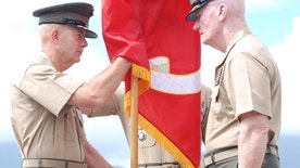 Lt. Gen. David Berger, left, receives the U.S. Marines Forces Pacific flag from outgoing commander Lt. Gen. John Toolan during a change of command ceremony in Kaneohe Bay, Hawaii on Friday, Aug. 26, 2016. The U.S. Marine Corps' new commander for the Pacific says he aims to carry on his predecessor's momentum on helping allies and partners develop their amphibious skills. (AP Photo/Audrey McAvoy)