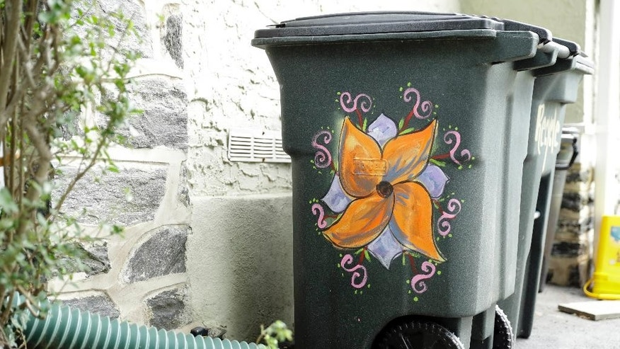 In this Thursday, Aug. 25, 2016, shows Esther Cohen-Eskin's garbage can that was defaced with a large swastika and then she repainted as a flower in Havertown, Pa. The neighborhood has rallied around the Jewish family and also painted their trashcans to show their support. (AP Photo/Matt Rourke)