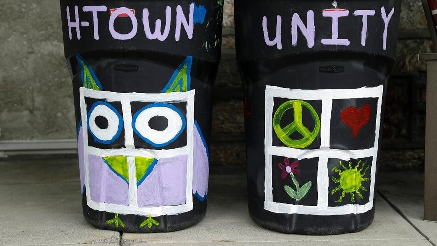 This Thursday, Aug. 25, 2016 photo, shows Megan Connell's trashcan that she painted to show support for her neighbor who's trashcan were defaced with a large swastika in Havertown, Pa. Esther Cohen-Eskin's painted a flower over the swastika on her garbage can and her neighborhood has rallied around the Jewish family by painting their trashcans in support. (AP Photo/Matt Rourke)