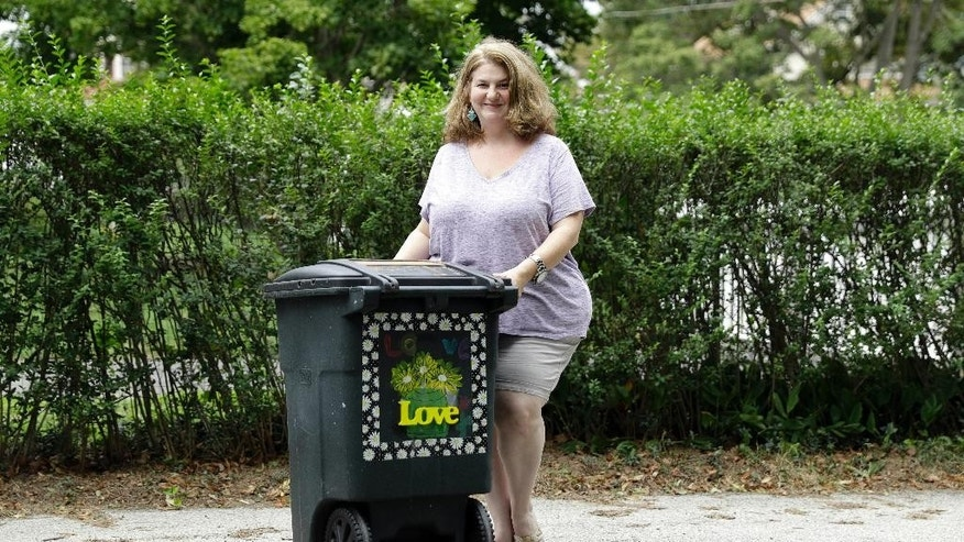 In this Thursday, Aug. 25, 2016 photo, Jenny Farley poses for a photograph with her trashcan she decorated to show support for her neighbor's who's garbage can was defaced with a large swastika in Havertown, Pa. Esther Cohen-Eskin's painted a flower over the swastika on her garbage can and her neighborhood has rallied around the Jewish family by painting their trashcans in support. (AP Photo/Matt Rourke)