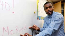 Dwayne Reed poses for a portrait at Stenson Elementary School in Skokie, Ill., Thursday, Aug. 25, 2016. Reed, who starts his first year as a student teacher this fall semester, wrote a rap welcoming his fourth graders to school. His three-minute video was posted on YouTube this week and by Thursday morning had more than 363,000 views. (AP Photo/Tae-Gyun Kim)