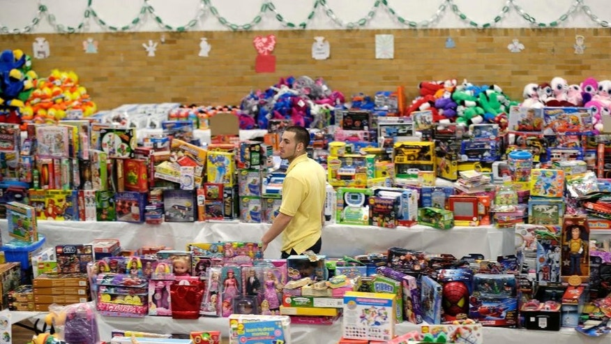 FILE - In this Friday, Dec. 21, 2012 file photo, volunteer Anthony Vessicchio of East Haven, Conn., walks past tables full of donated toys at the town hall in Newtown, Conn. Donors from around the world sent gifts, including teddy bears for children in the community of about 28,000. More than 60,000 bears accumulated in a warehouse before eventually being sent to hospitals and other charities around the globe. (AP Photo/Seth Wenig)