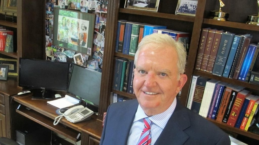 In this Aug. 4, 2016 photo, attorney Andy Savage poses in his office in Charleston, S.C. Savage represents Michael Slager, a white former policeman facing a murder charge in the shooting of a black motorist, as well as victims and the families of victims in the June 2015 shootings at Charleston's Emanuel AME Church. Trials in both cases are scheduled to begin in Charleston this fall. (AP Photo/Bruce Smith)