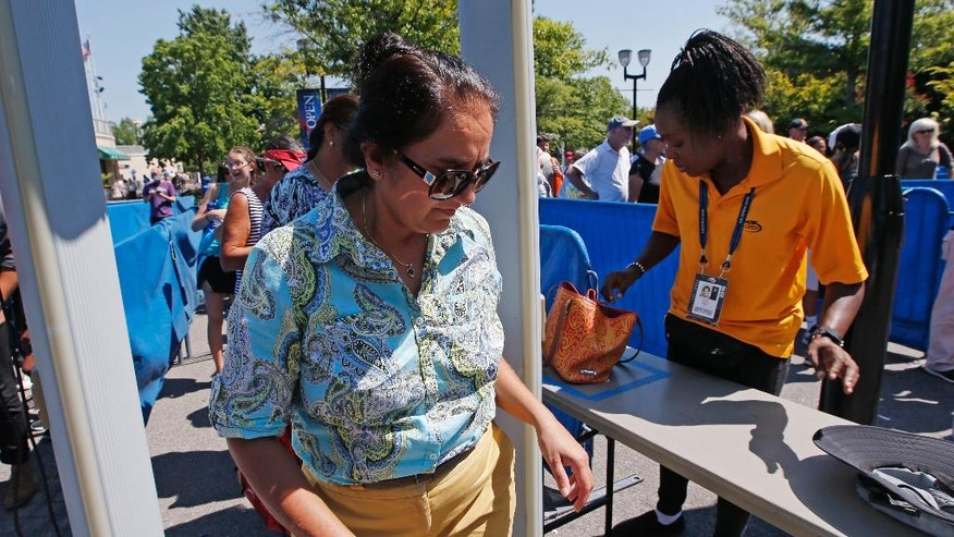 In this Wednesday, Aug. 24, 2016 photo, a woman passes through a metal detector for security screening while entering the grounds of the Billie Jean King National Tennis Center in New York during qualifying rounds for the U.S. Open Tennis Tournament. With more than 700,000 fans expected, the U.S. Open tennis tournament poses unique security challenges for officials charged with making the grounds safe. (AP Photo/Kathy Willens)