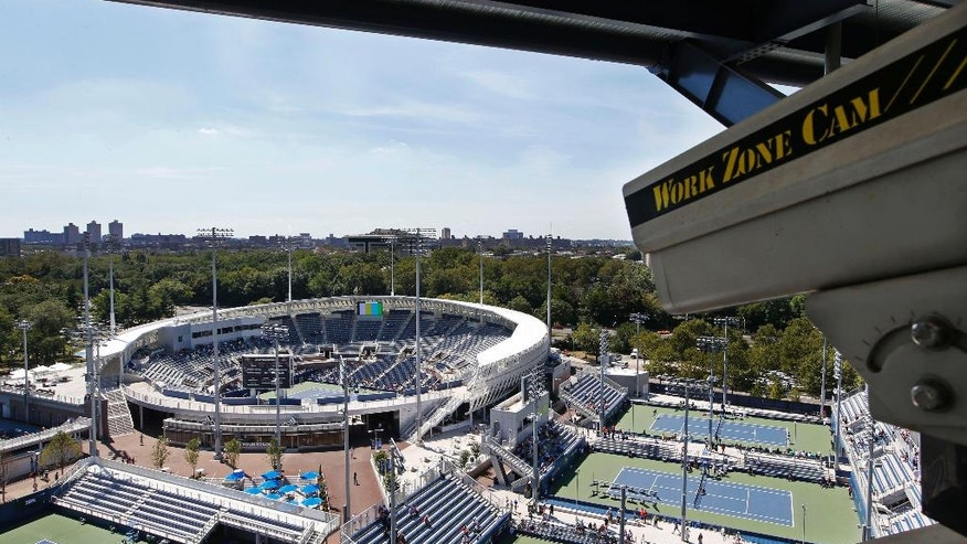 In this Wednesday, Aug. 24, 2016 photo, a closed circuit construction camera peers out at the Grandstand stadium during qualifying rounds at the Billie Jean King National Tennis Center in New York. More than a half million fans over two weeks are expected at this year's U.S. Open tennis tournament and security officials are ramping up efforts to make the grounds safer than ever. Cameras such as this one will allow officials in the command center to have varying views of the grounds. (AP Photo/Kathy Willens)