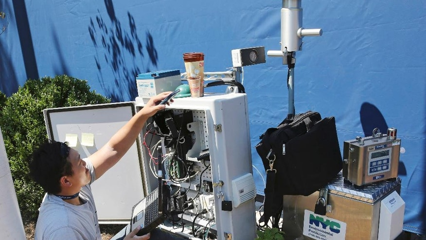 In this photo taken Wednesday, Aug. 24, 2016, a technician programs a radiation detection device at the entrance to the the Billie Jean King National Tennis Center in New York. The devices, installed by New York City's Department of Environmental Protection, are among many measures being taken to enhance security for the more than 700,000 fans that are expected to attend this year's U.S. Open Tennis Tournament. (AP Photo/Kathy Willens)
