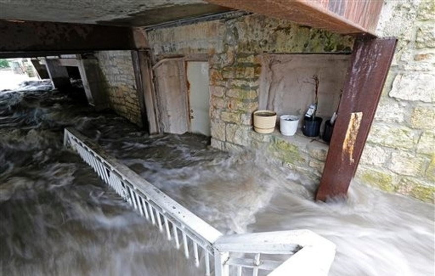 Floodwater pours into the basement of Schera's Algerian American Restaurant & Bar, as the Turkey River swells causing flood damage to the basements of nearby businesses in Elkader, Iowa, on Friday, Aug. 26, 2016. (Mike Burley/Telegraph Herald via AP)