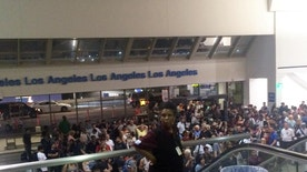 A crowd of people wait in Terminal 1 where passengers were being rescreened by security at Los Angeles International Airport after reports that a gunman opened fire Sunday, Aug. 28, 2016. The active shooter reports turned out to be false but caused panicked evacuations at Los Angeles International Airport on Sunday night, while flights to and from the airport were delayed. A search through terminals brought no evidence of a gunman or shots fired, Los Angeles police spokesman Andy Neiman said. (Bari Ross via AP)