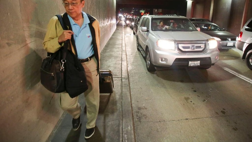 A man with his luggage walks toward Los Angeles International Airport, Sunday, Aug. 28, 2016. Reports of a gunman opening fire that turned out to be false caused panicked evacuations at Los Angeles International Airport on Sunday night, while flights to and from the airport were delayed. A search through terminals brought no evidence of a gunman or shots fired, Los Angeles police spokesman Andy Neiman said.  (AP Photo/Ringo H.W. Chiu)
