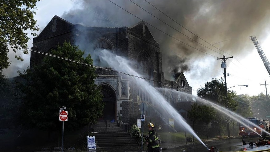 Firefighters battle a blaze at the Christ Liberation Fellowship Church in Philadelphia, Monday, Aug. 29, 2016. (AP Photo/Matt Rourke)