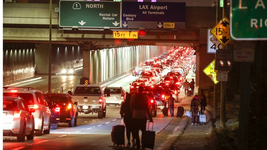 Aug. 28, 2016: Passengers pull their luggage and walk toward Los Angeles International Airport.