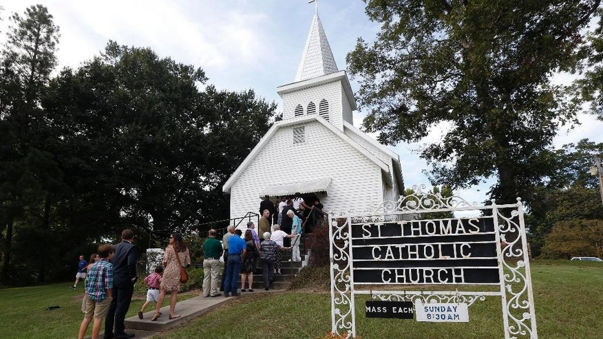People stand in line to attend a vigil for the deceased held at St. Thomas Catholic Church in Lexington, Miss., for Sister Margaret Held and Sister Paula Merrill, Sunday, Aug. 28, 2016. The two nuns, from different orders, were found murdered in the Durant, Miss., house they rented, on Thursday. Over 300 people attended the service. Although authorities have arrested a suspect, they speculate on the motive of the deaths of the two nurse practitioners, who worked the poor in a clinic in Lexington. (AP Photo/Rogelio V. Solis)