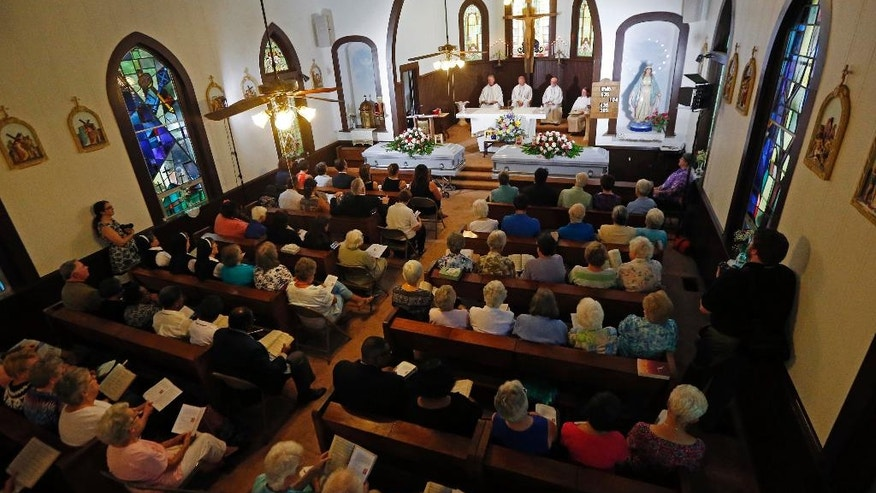 Bishop Joseph Kopacz of the Jackson, Miss., Catholic Diocese, center, presides at a vigil for the deceased held at St. Thomas Catholic Church in Lexington, Miss., for Sister Margaret Held and Sister Paula Merrill, Sunday, Aug. 28, 2016. The two nuns, from different orders, were found murdered in the Durant, Miss., house they rented, on Thursday. Although authorities have arrested a suspect, they speculate on the motive of the deaths of the two nurse practitioners, who worked the poor in a clinic in Lexington. (AP Photo/Rogelio V. Solis)