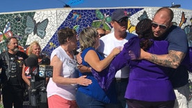 Relatives of Victoria Martens and her godmother Laura Bobbs, second from right, embrace at a children's park in Rio Rancho, New Mexico, following a news conference Monday, Aug. 29, 2016, to thank the community following the Albuquerque girl's horrific killing last week. Police found Victoria's battered and dismembered body inside the apartment she shared with her mother after responding Aug. 24, 2016, to a pre-dawn disturbance. (AP Photo/Mary Hudetz).