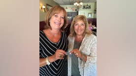 In this photo taken Monday, Aug. 22, 2016 and provided by Audrey Berk, Berk, left, of Queens, N.Y., and Laurie Lubin of Bellmore, N.Y., hold the World War II dog tags of Berk's father, Irving Isaacs in Bellmore, N.Y. Lubin found the tags on a New York City beach in the summer of 1966 and spent the next 50 years trying to return them. Lubin finally tracked down Isaacs' daughter with the help of The Associated Press and gave her the dog tags at a Bellmore restaurant on Aug. 22. (Audrey Berk/Laurie Lubin/Clifford Kaplan via AP)