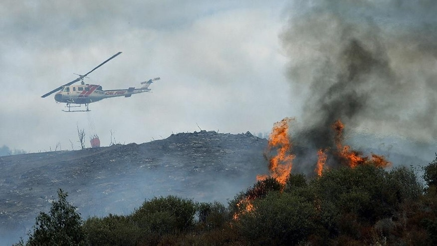 A water dropping helicopter heads back to get more water as a wildfire burns near homes in the brush in Beaumont, Calif., Tuesday, Aug. 30, 2016. (Terry Pierson/The Press-Enterprise via AP)