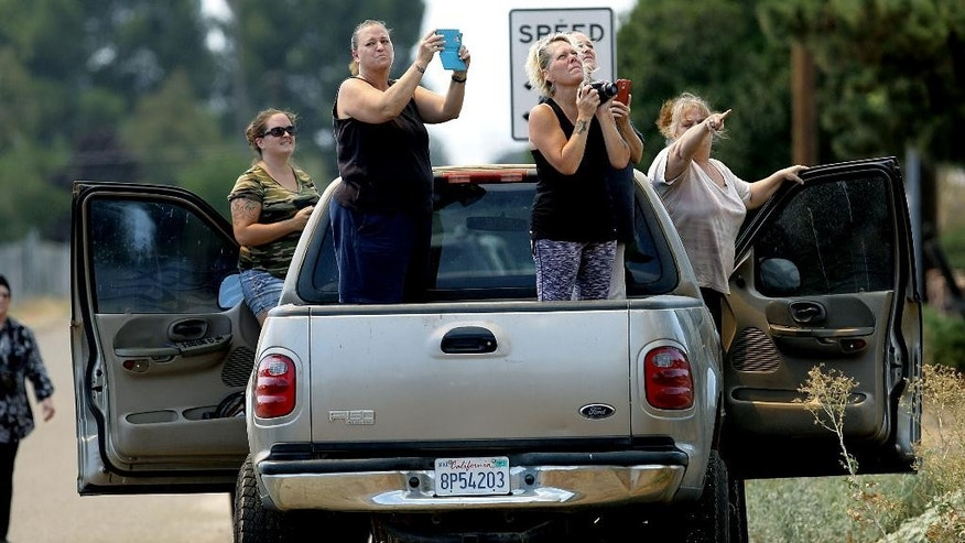 Women take pictures of a wildfire from a pickup truck as the fire burns near homes in the brush in Beaumont, Calif., Tuesday, Aug. 30, 2016. (Terry Pierson/The Press-Enterprise via AP)