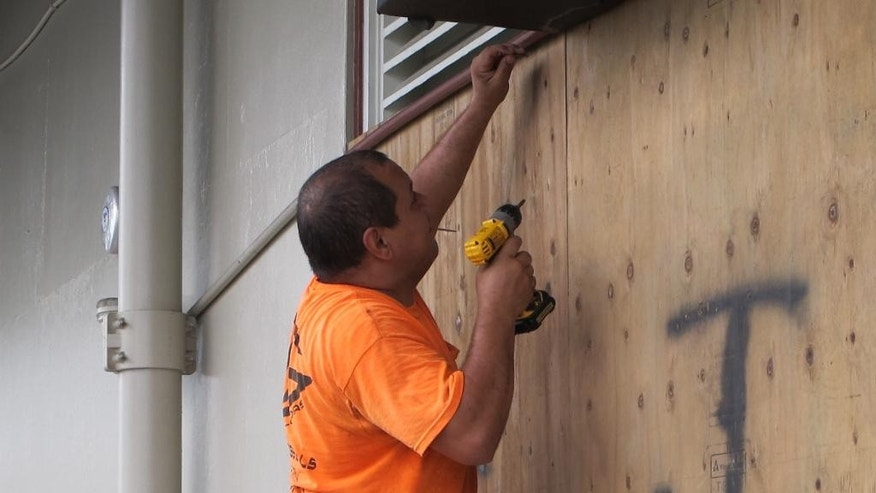 Giuseppe Manone boards up the windows of a store in Hilo, Hawaii as Hurricane Madeline approached the Big Island on Wednesday, Aug. 31, 2016. Drier air and strong upper atmosphere winds are weakening Hurricane Madeline as it approaches Hawaii. (AP Photo/Audrey McAvoy)
