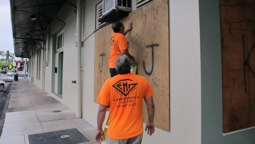 Workers board up the windows of a store in Hilo, Hawaii as Hurricane Madeline approached the Big Island on Wednesday, Aug. 31, 2016. Drier air and strong upper atmosphere winds are weakening Hurricane Madeline as it approaches Hawaii. (AP Photo/Audrey McAvoy)