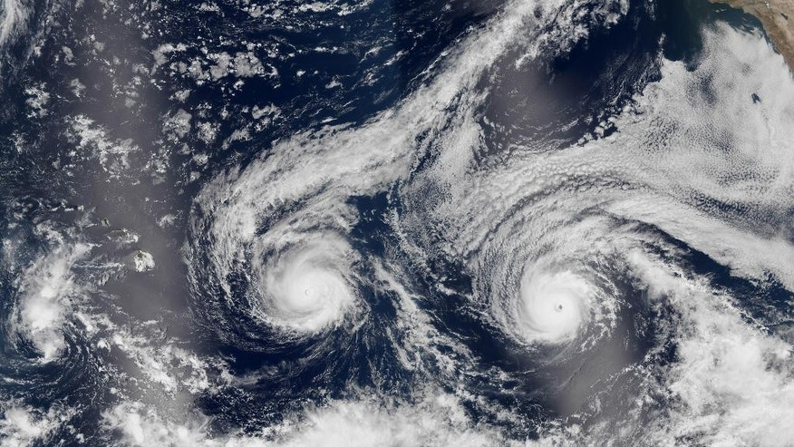 This satellite image taken Monday, Aug. 29, 2016 and released by NASA shows Hurricane Madeline, left, and Hurricane Lester over the Pacific Ocean in a composite built from two overpasses by the Visible Infrared Imaging Radiometer Suite on the Suomi NPP satellite. The National Weather Service issued a hurricane warning as the storm dubbed Madeline churned west Tuesday, Aug. 30, 2016, toward the island, urging residents to rush through preparations to protect themselves and their property and expect hurricane conditions within the next 36 hours. (NASA via AP)