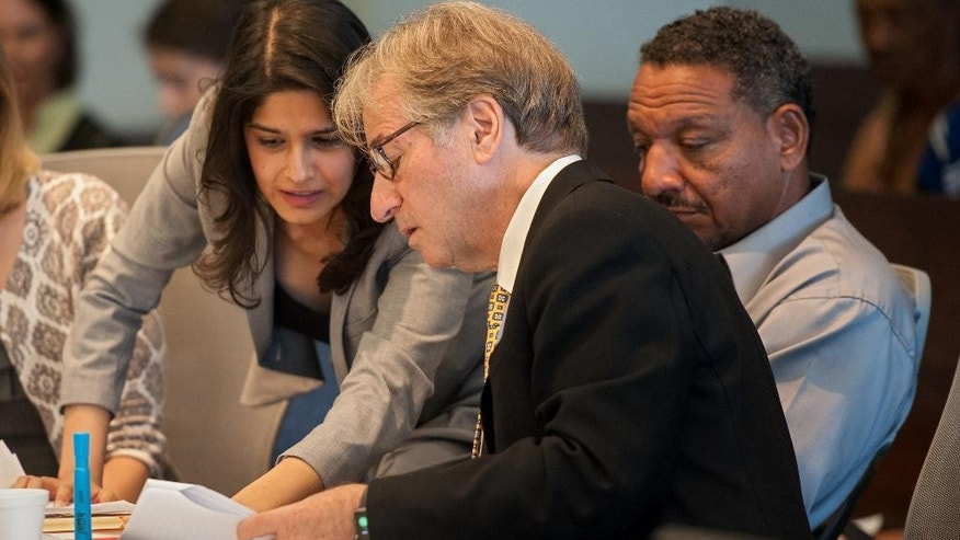 Attorneys Seema Saifee and Barry Scheck confer as Darryl Howard looks on during a hearing Tuesday, Aug. 30, 2016, at the Durham County Courthouse in Durham, N.C. Jermeck Jones, an ex-convict linked to a slain woman through DNA testing, is refusing to answer questions at a hearing that could free Howard, who was sentenced to prison 21 years ago for the killing. (Kaitlin McKeown/The Herald-Sun via AP)
