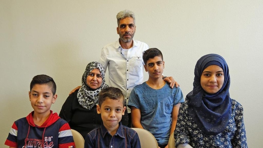Nadim Fawzi Jouriyeh, rear, a Syrian refugee that arrived with his family in the United States this week, poses with the family Wednesday Aug. 31, 2016, in El Cajon, Calif. The family members are his wife Rajaa Abdo Altaleb, back left, son Mohammad Fawzi Jouriyeh, back right, daughter Hanan Nadim Jouriyeh, right, Farouq Nadim Jouriyeh, front center, and Hamzeh Nadim Jouriyeh, front left. San Diego's newest Syrian refugee arrivals include the Jouriyeh family of six from the city of Homs. The family tells the AP they feel welcome in their new community of El Cajon, where many refugees are resettled where store signs are in Arabic and many speak their language. (AP Photo/Lenny Ignelzi)