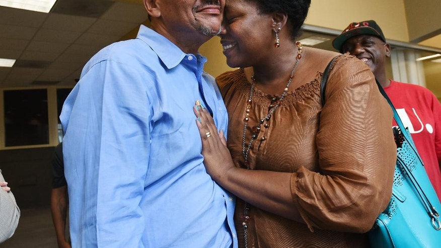 Darryl Howard, gets a hug from his wife Nannie as prepare to leave the Durham County Detention Center, Wednesday, Aug. 31, 2016, in Durham, N.C., after a judge threw out Howard's conviction in a double-murder case tried 21 years ago and ordered Howard's release because of DNA evidence unavailable at his 1995 murder trial. (Chuck Liddy/The News & Observer via AP)
