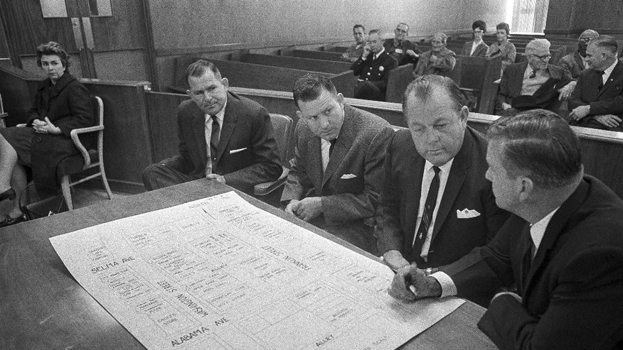 FILE - In a Dec. 9, 1965 file photo, three defendants go over a street diagram of area in Selma, Ala., where the clubbing death of a Unitarian Universalist minister Rev. James Reeb took place last March during civil rights strife. From left: Stanley and Namon Hoggle, brothers, and Elmer Cook, all defendants, and Robert Radford, investigator.  An obituary says Namon Hoggle, the last of three men acquitted in the infamous civil rights slaying, died Tuesday, Aug. 30, 2016. He was 81.  (AP Photo/Horace Cort, File)